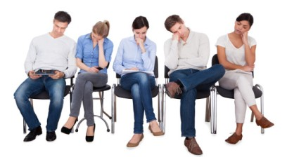 Full length of bored businesspeople sitting on chairs against white background